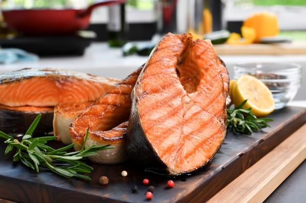 Стейки из лосося с ингредиентами на деревянной разделочной доске на кухне