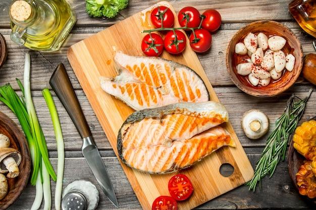 Стейки из лосося на гриле с различными овощами и специями. на деревянном столе.