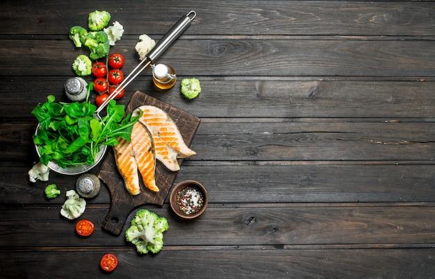 Стейки из лосося на гриле с овощами, специями и зеленью. на деревянном фоне.