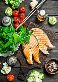 Стейки из лосося на гриле с овощами, специями и зеленью. на деревянном столе.