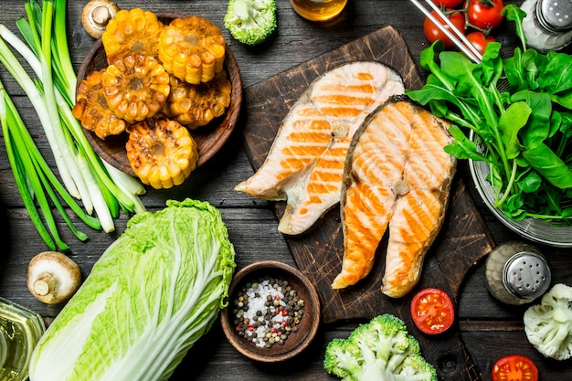 Стейки из лосося на гриле с овощами, специями и зеленью. на деревянном.