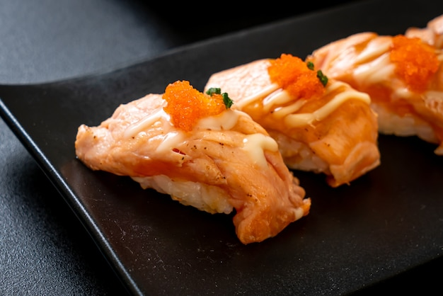 Grilled salmon sushi on black plate - japanese food style