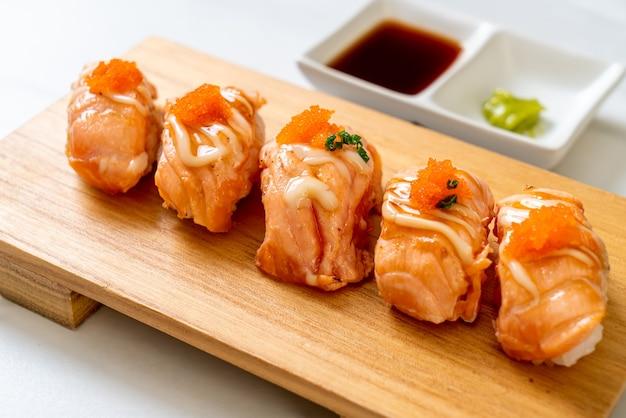 Суши с лососем на гриле на деревянной тарелке - стиль японской кухни