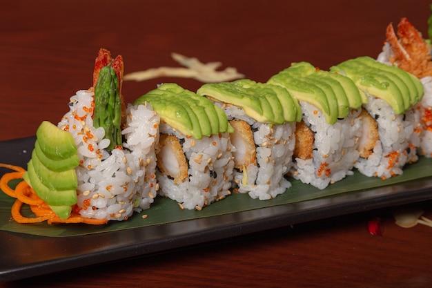 木製のテーブルにアボカド、海老の天ぷら、チーズを巻いたサーモン寿司のグリル。孤立した画像