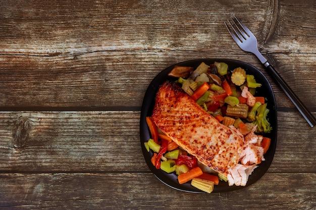 Жареный лосось с азиатскими овощами жаркое на черной тарелке с вилкой. скопируйте пространство. вид сверху.