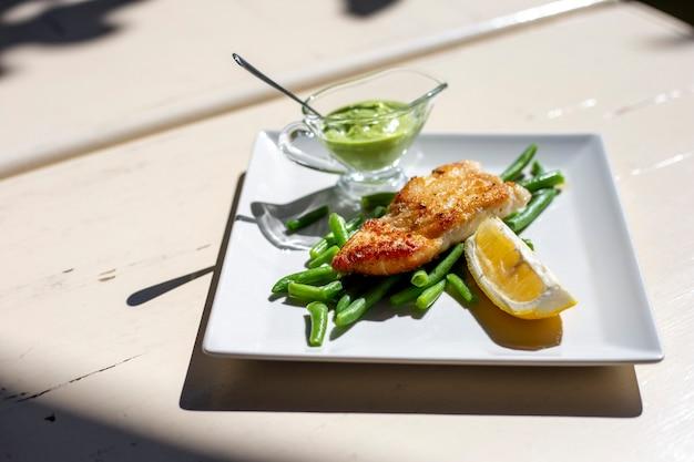 Лосось на гриле с зеленой фасолью, лимоном и зеленым соусом на белой квадратной тарелке на столе снаружи