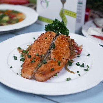 Grilled salmon with herbs and spices in white plate
