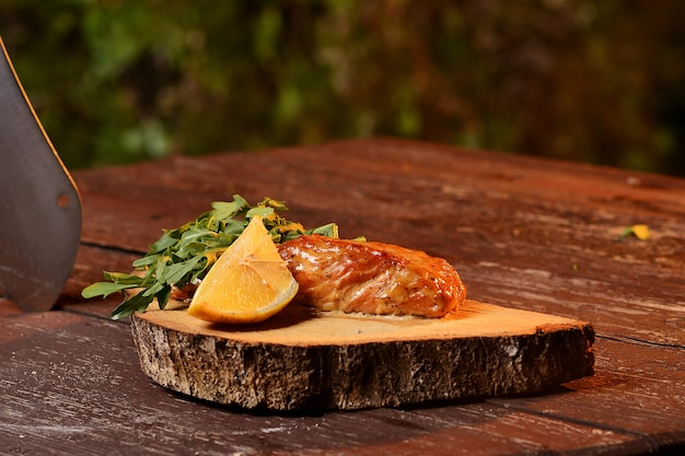 Grilled salmon with lemon and arugula. on a wooden board.