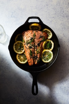 Grilled salmon with lemons in a black pot on a white surface