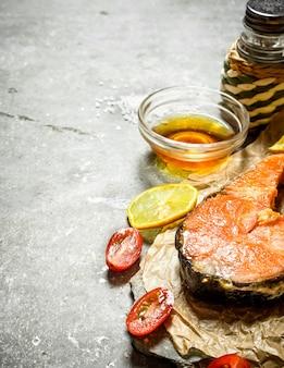 サーモンのグリル、オリーブオイル、トマト、レモン、スパイス。石のテーブルの上。
