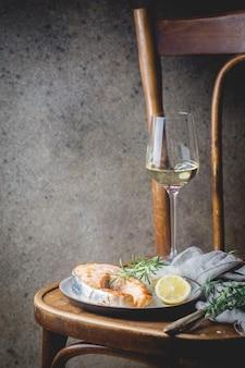 素朴な装飾の皿にご飯と白ワインを添えたサーモンのグリル