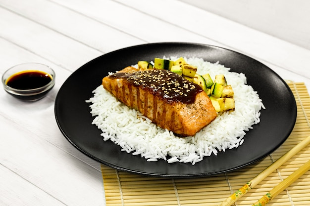 Grilled salmon with rice, teriyaki sauce, and fried zucchini