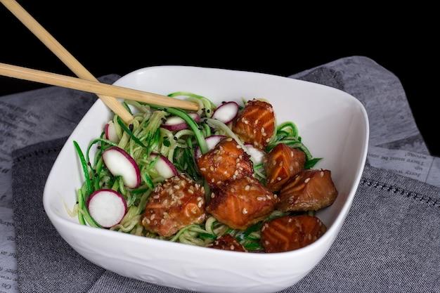 Лосось на гриле с семенами кунжута с салатом, спагетти с огурцами и белой миской с редисом