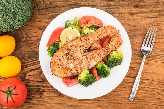 접시에 다양한 야채와 연어 구이