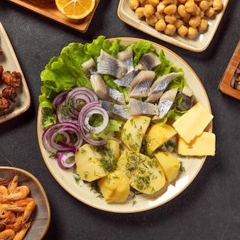 Жареная соленая рыба с картофелем и луком крупным планом