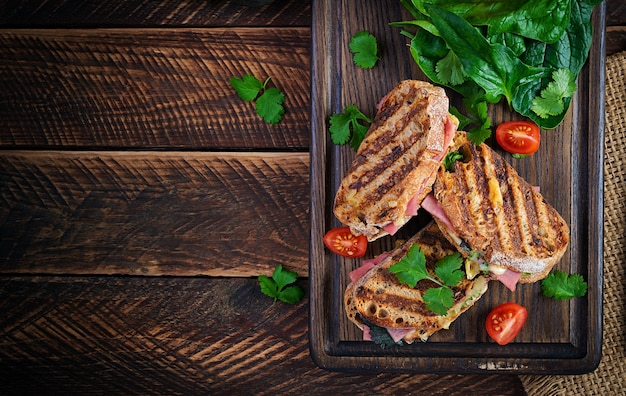 Grilled sandwich panini with ham, tomato, cheese and spinach. delicious breakfast or snack. top view, copy space, overhead