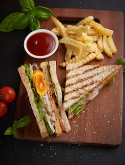 Grilled and sandwich with bacon, fried egg, tomato and lettuce served on wooden cutting board