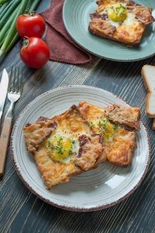 暗い木製のテーブルに卵、野菜、ベーコンのグリルサンドイッチ。おいしい朝食。テキストのための場所。