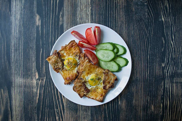 Grilled sandwich with egg, vegetables and bacon on a dark wood