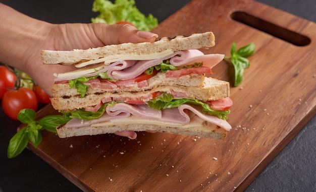 木製のまな板にハム、チーズ、トマト、レタスのグリルサンドイッチを添えて。