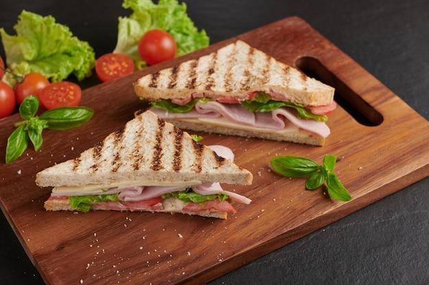 Жареный сэндвич с ветчиной, сыром, помидорами и салатом на деревянной разделочной доске.