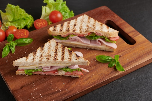 Grilled sandwich with ham, cheese, tomato and lettuce served on wooden cutting board.