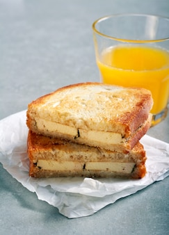 Grilled sandwich with tofu filling and orange juice