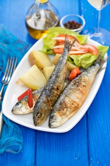 Grilled sardines with boiled potato and salad on white plate