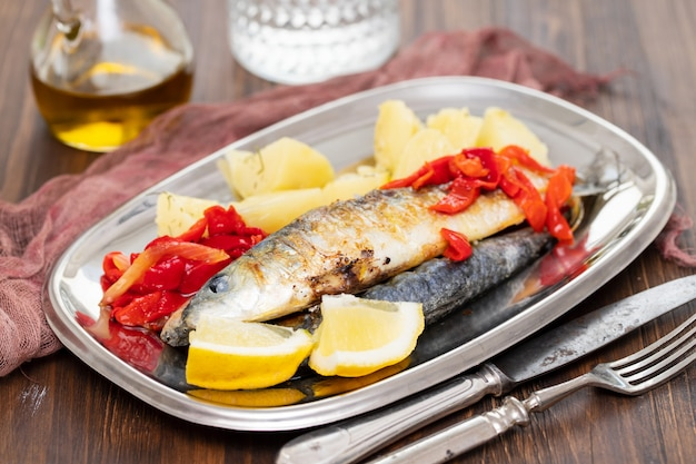 Grilled sardines with pepper and boiled potato on dish