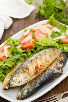 Grilled sardines with salad on white dish