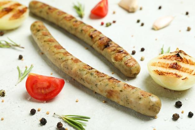 Колбаса на гриле и специи на белом фоне