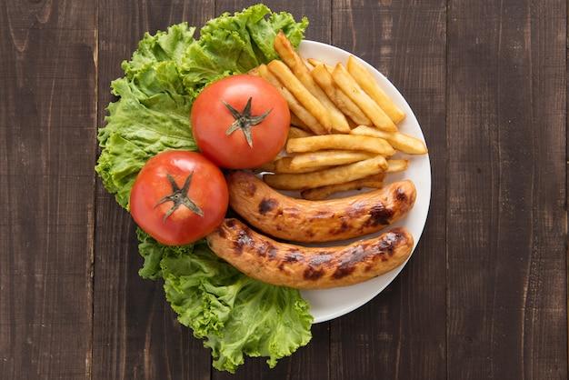 グリルソーセージと野菜の木製の背景にフライドポテト