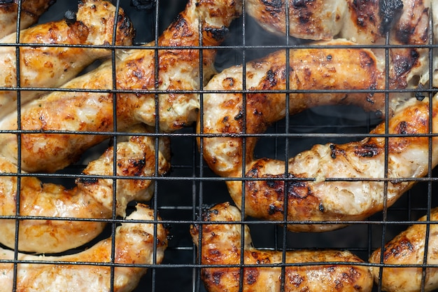Grilled sausage on barbecure, top view, close up
