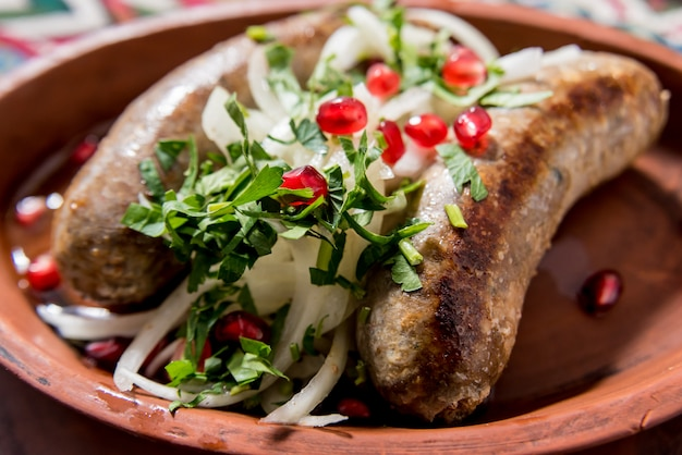 Grilled sausage in a clay pot. georgian restaurant.