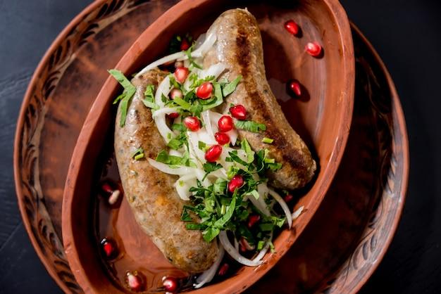 Жареная колбаса в глиняном горшочке. грузинский ресторан.