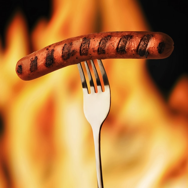 Жареная колбаса на вилке на фоне огня