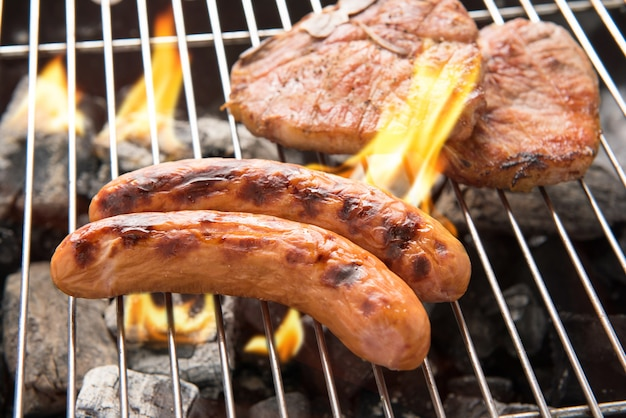 Grilled sausage and pork chop on the flaming grill