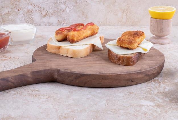 木の板にケチャップを添えたグリルソーセージサンドイッチ。