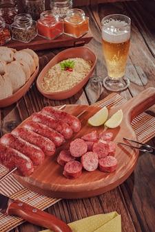 木の板にグリルしたソーセージの串焼き、ビール、パン、ファロファのブラジル風バーベキュー