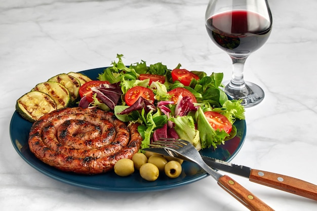 Grilled sausage with chopped tomatoes and herbs on a blue plate with a glass of red wine on a light table