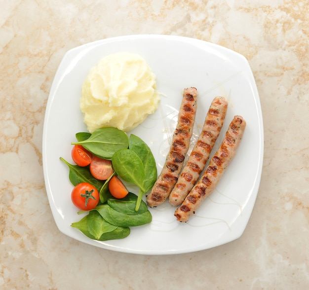 Grilled sausage with mashed potatoes, spinach and tomatoes