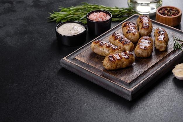 어두운 배경에 허브와 야채를 추가한 구운 소시지. 그릴 음식, 바베큐