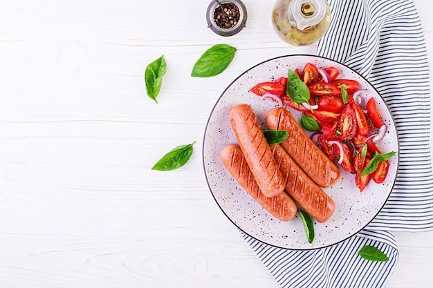 Жареная колбаса с помидорами, салатом из базилика и красным луком