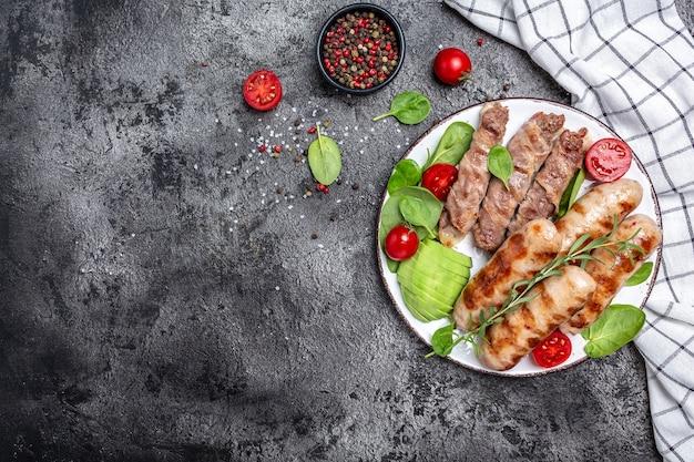 Колбаски на гриле и мясные рулеты, завернутые в бекон, чевапчичи или кебаб кофта. полезные жиры, чистое питание для похудения. баннер, меню, место рецепта для текста, вид сверху.