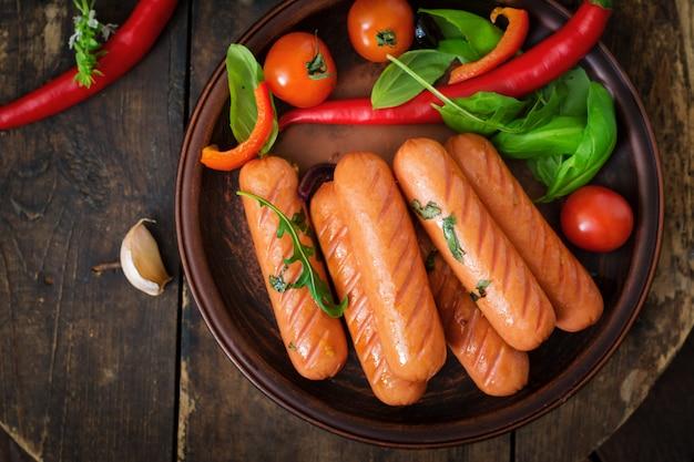 Жареные колбаски и овощи на деревянном столе в деревенском стиле.