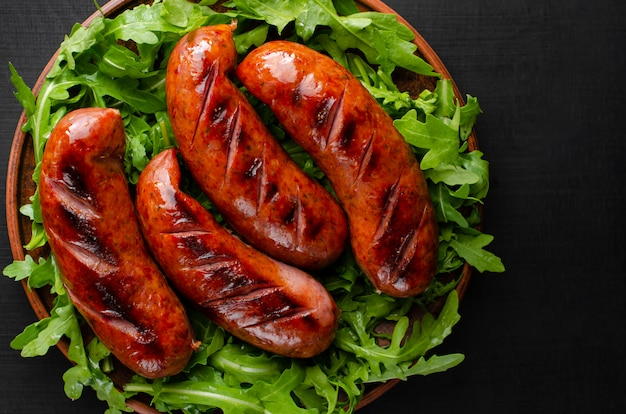 Grilled sausages and arugula on black background. top view.