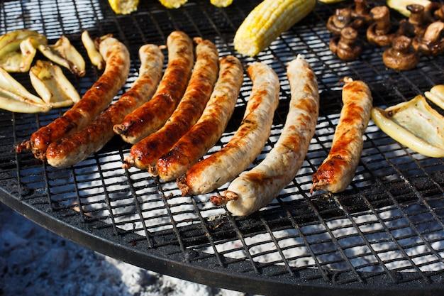Колбаски гриль на барбекю на открытом воздухе