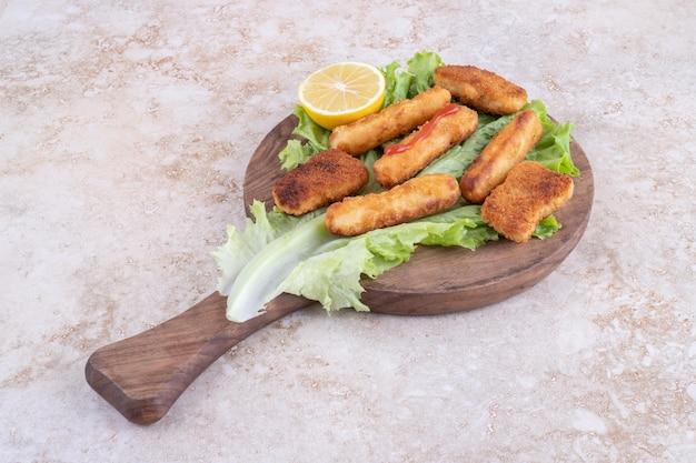 Salsicce alla griglia, bastoncini di formaggio e bocconcini di pollo su una foglia di lattuga.
