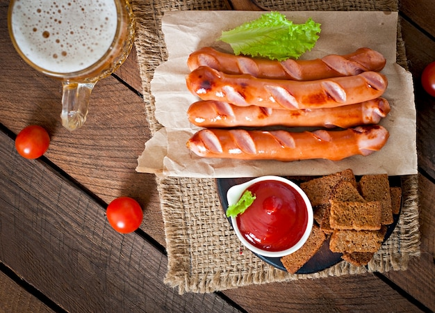 Grilled sausages, crackers and beer on a wooden table in rustic style.
