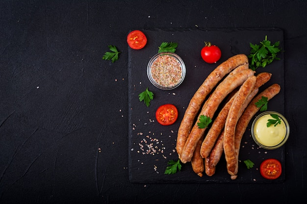 Grilled sausages on dark background. oktoberfest. flat lay. top view
